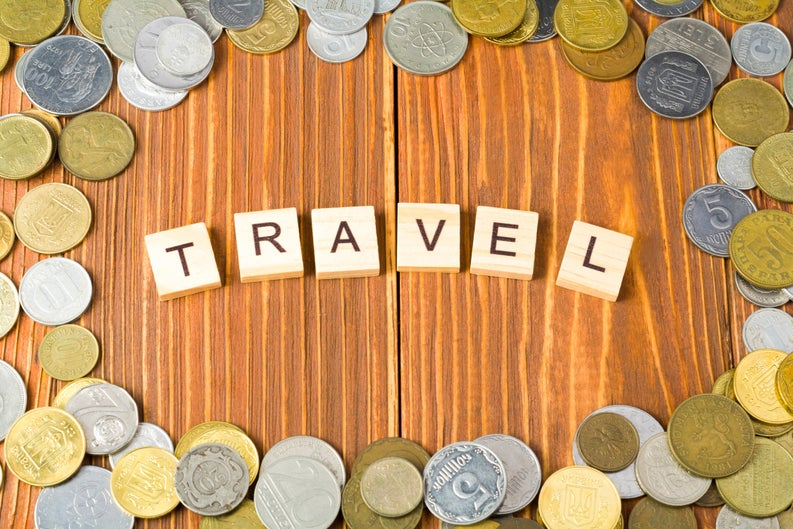 """scrabble tiles spelling """"travel"""" surrounded by coins"""