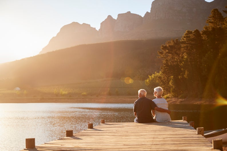 senior man and woman sitting at the end of a dock on a lake_retirement relaxing vacation