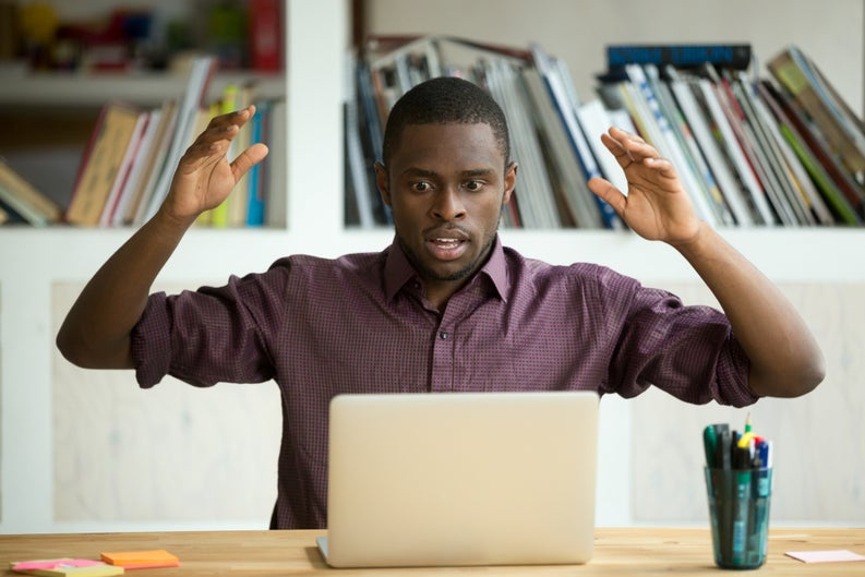 Shocked man with his hands in the air staring at his laptop