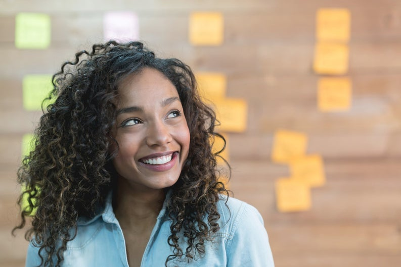 A smiling young woman in front of a wall covered in colorful sticky notes.