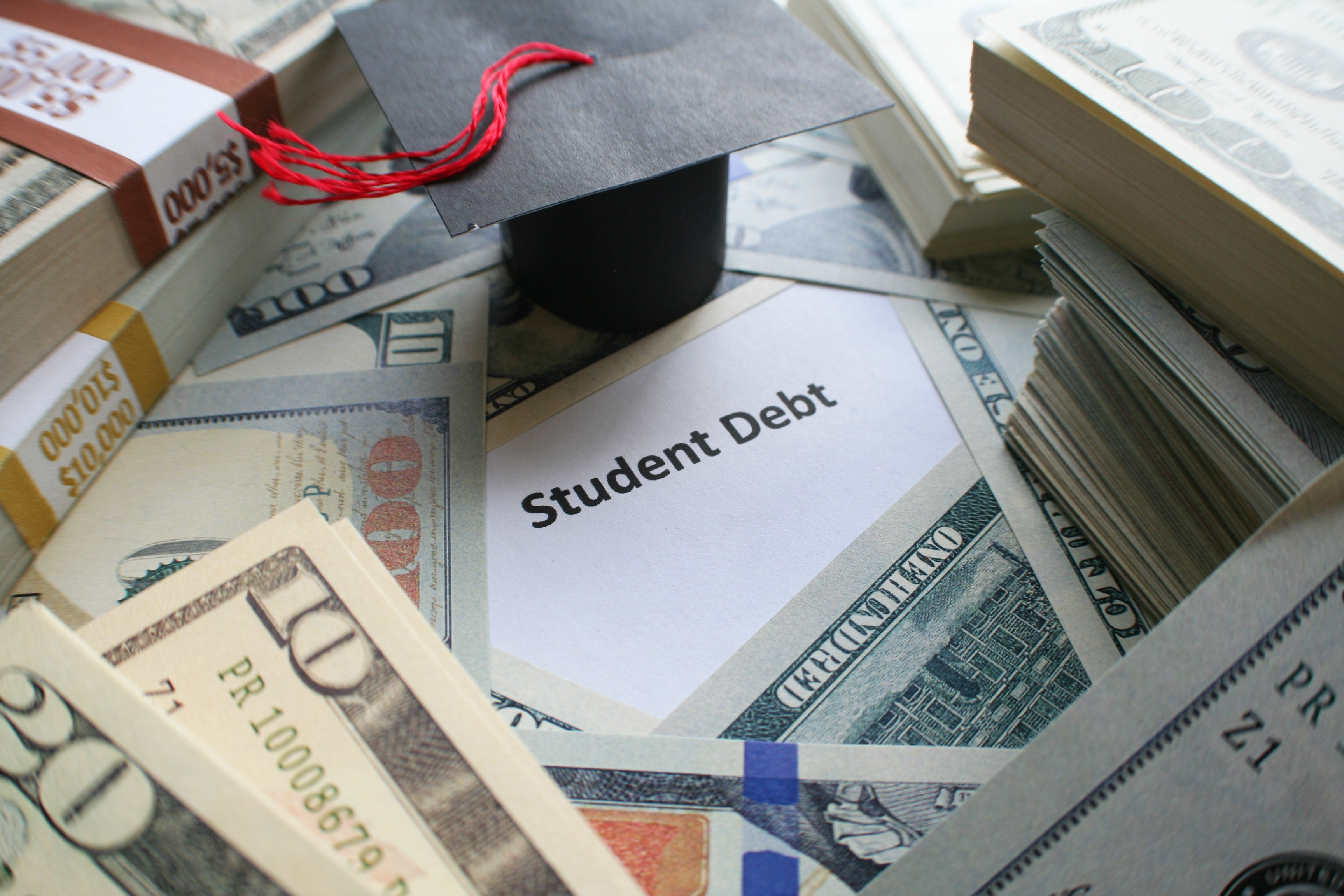 A piece of paper that says student debt surrounded by U,S. currency.