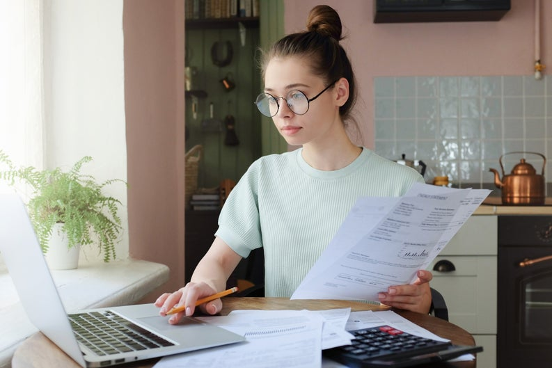 woman with glasses at computer going over budget
