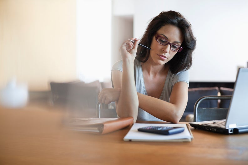 Woman holding a pen with papers and a calculator in front of her.