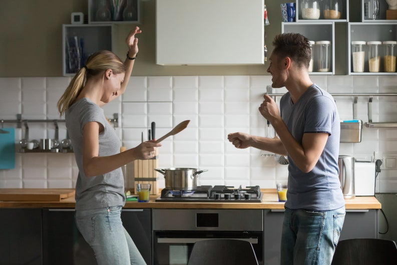 young man and woman smiling and dancing in kitchen -- couple celebrating happy