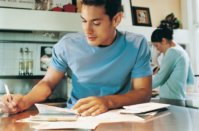 young man sitting at kitchen table writing a check
